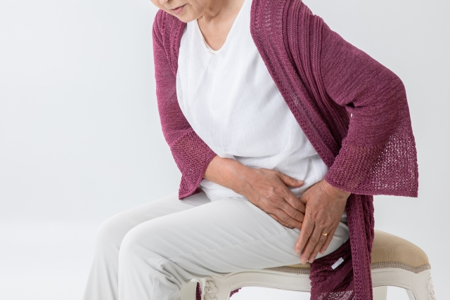 股関節を押さえる高齢者